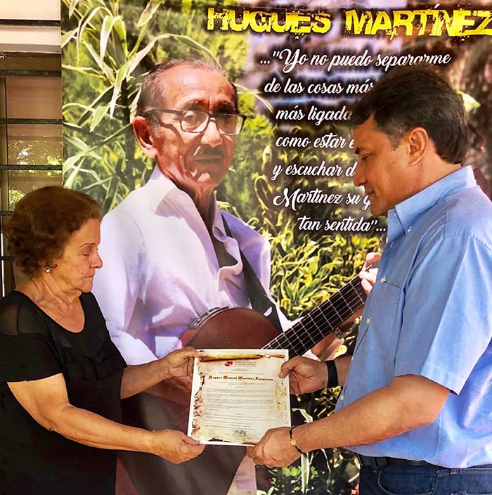 Rodolfo Molina Araújo, entrega Nota de Estilo a Katia Montero, donde se exalta la vida y obra del fallecido guitarrista Hugues Martínez Sarmiento